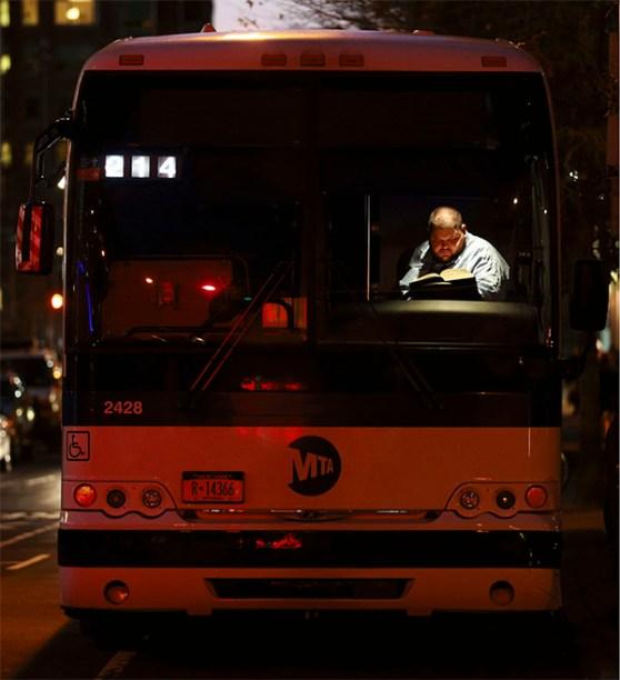 Conductor de autobús de Nueva York leyendo en un descanso