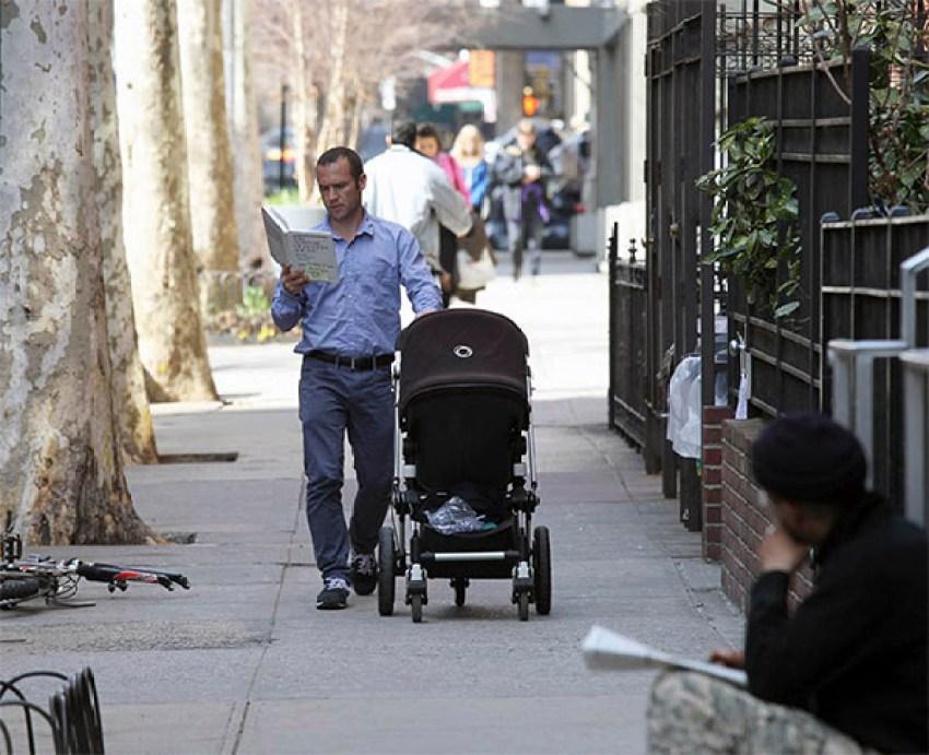 Hombre con coche de bebé leyendo en Nueva York