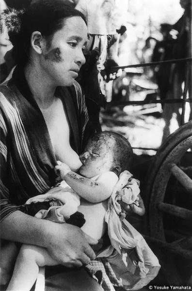 UNA MADRE Y SU HIJO ESPERAN PACIENTEMENTE A SER ATENDIDOS Aproximadamente a 3,6 kilómetros al norte del lugar del impacto. Fotografía tomada el día después del bombardeo en el centro de socorro provisional situado frente a la estación de ferrocarriles de Michinoo. Tanto la madre como el bebé tenían heridas. El bebé, de cuatro meses, quedó sin fuerzas para mamar y murió unos diez días después. 9 de agosto de 1945.
