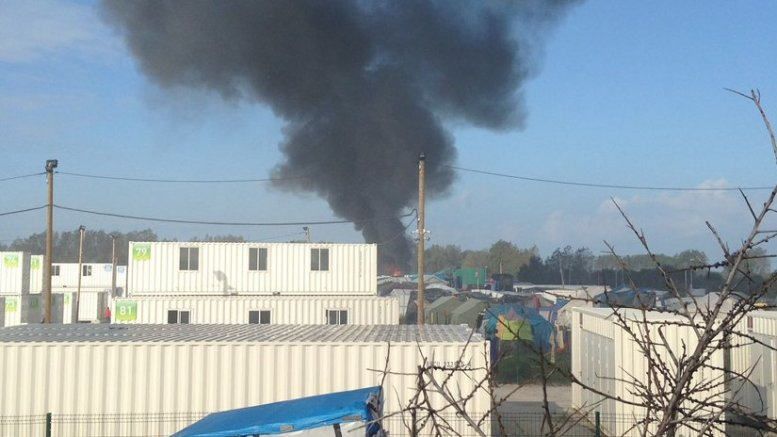 "A plume of smoke rises from the Sudanese quarter of ""The Jungle"" in Calais as police begin demolishing the refugee camp.  Photo credit: Alexandra Vuillard."