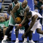 Boston Celtics center Shaquille O&#039;Neal (C) holds onto the ball as Orlando Magic forward Brandon Bass (R) goes for the ball during the first half of NBA basketball action in Orlando, Florida December 25, 2010.