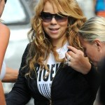 Mariah Carey heads into her Manhattan apartment building protected by a large entourage. (July 6, 2011)