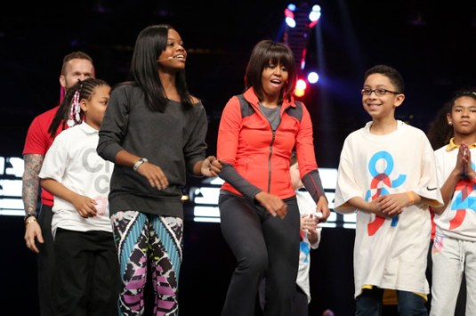 Gabby Doulas (L) and first lady Michelle Obama (C) dances with school children during a debut of a school exercise program February 28, 2013 in Chicago, Illinois. Obama unveiled a new program called 'Let's Move Active Schools' to help schools create a physical activity programs for students.
