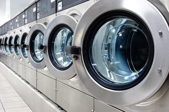 A row of industrial washing machines in a public laundromat.