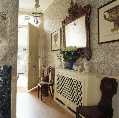 Image: Large carved wood antique mirror above radiator with painted fretwork cover in hall with ...