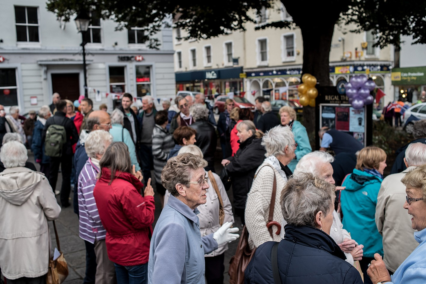 Pensioners crowded into town square, with balloons