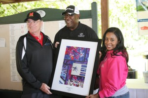 Les Merton, President of Adrian L. Merton, Inc. receiving a special gift from members of the Boys & Girls Club in appreciation for his title sponsorship of the golf tournament. L to R: Les Merton (President - Adrian L. Merton, Inc.) Reginald Broddie (CPO - BGCAA), Tierra Snowden (Director of Program Operations - BGCAA).