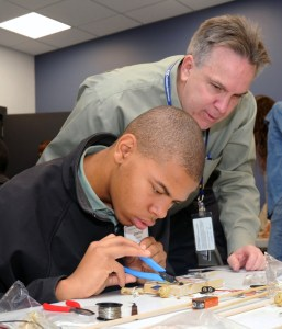 Systems Engineering Manager Mark Strickenburg assists Joshua Lewis with his radio build as part of the Northrop Grumman STEM event.