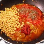 Then add, tomato puree, tomatoes, chickpeas, basil, seasoning & water.