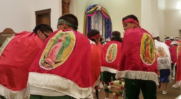 The matachines, crouching in respect to the Virgin, approach the shrine prior to the dance.
