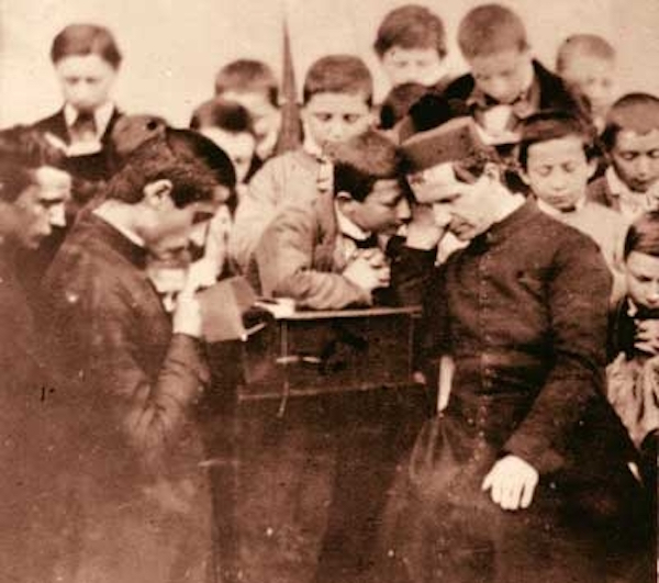 Don Bosco hearing confessions. Boys flocked to avail themselves of the Sacrament at a time when many adults confessied their sins to a priest rarely or not at all.