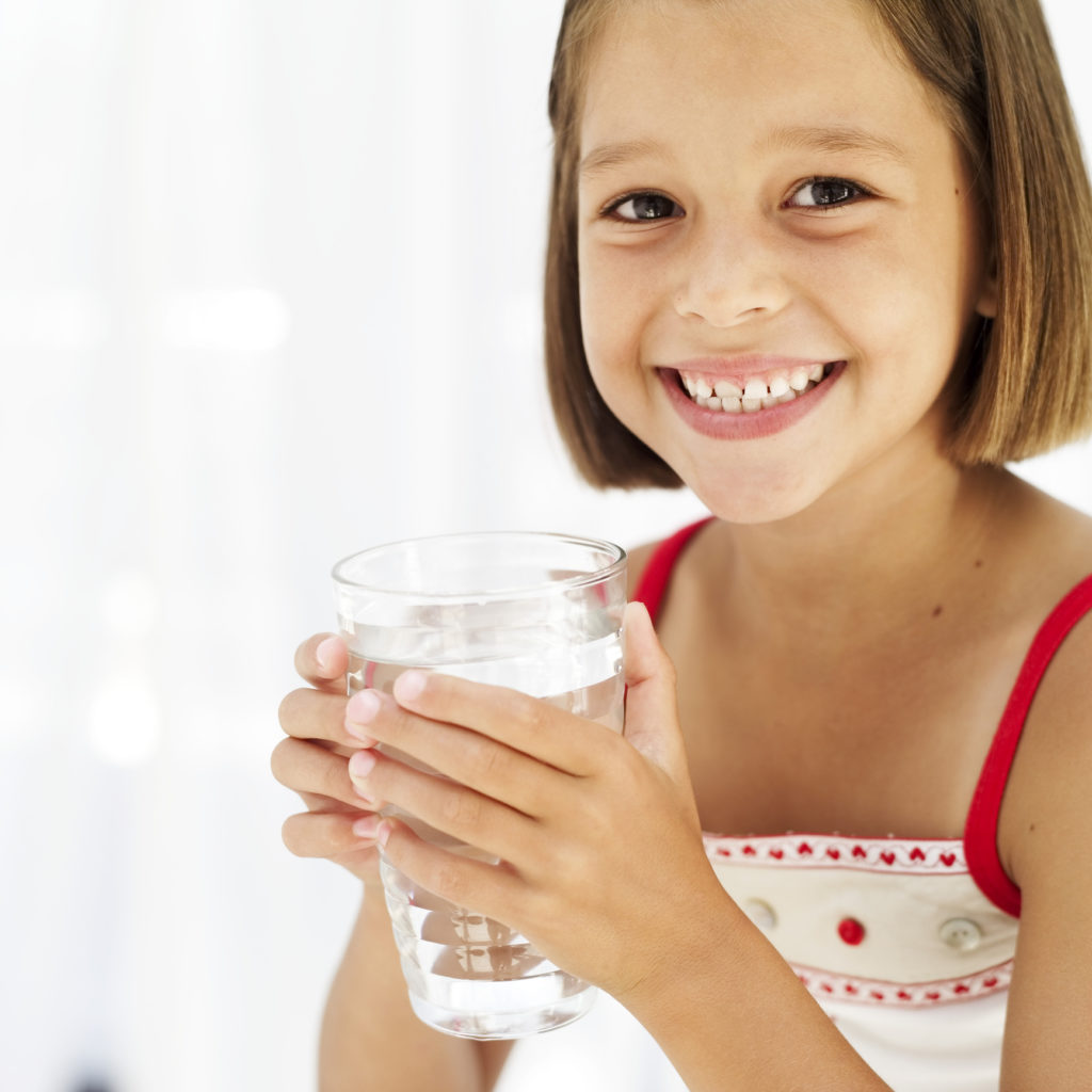 portrait of a young girl holding a glass of water