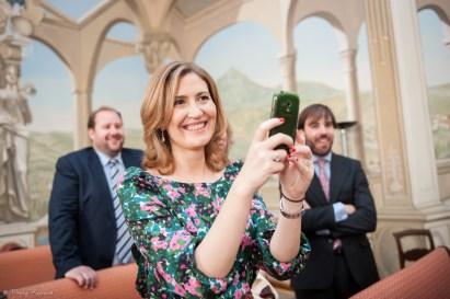 Photographie en couleur d'une invitée qui photographie avec son smartphone les mariés à la mairie de clermont-ferrand. Image spontanée professionnelle.