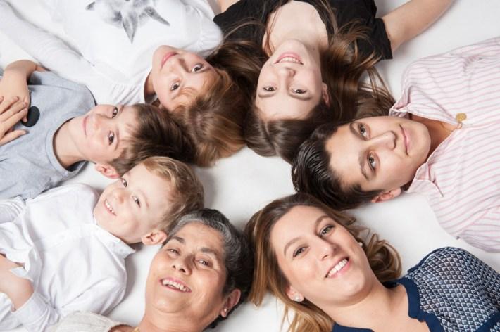 Photographie originale en studio d'une famille nombreuse - la grend-mère et ses cinq petits-enfants. Ils sont allongés par terre sur le dos en rond. © Fanny Reynaud photographe de portrait à clermont-ferrand.