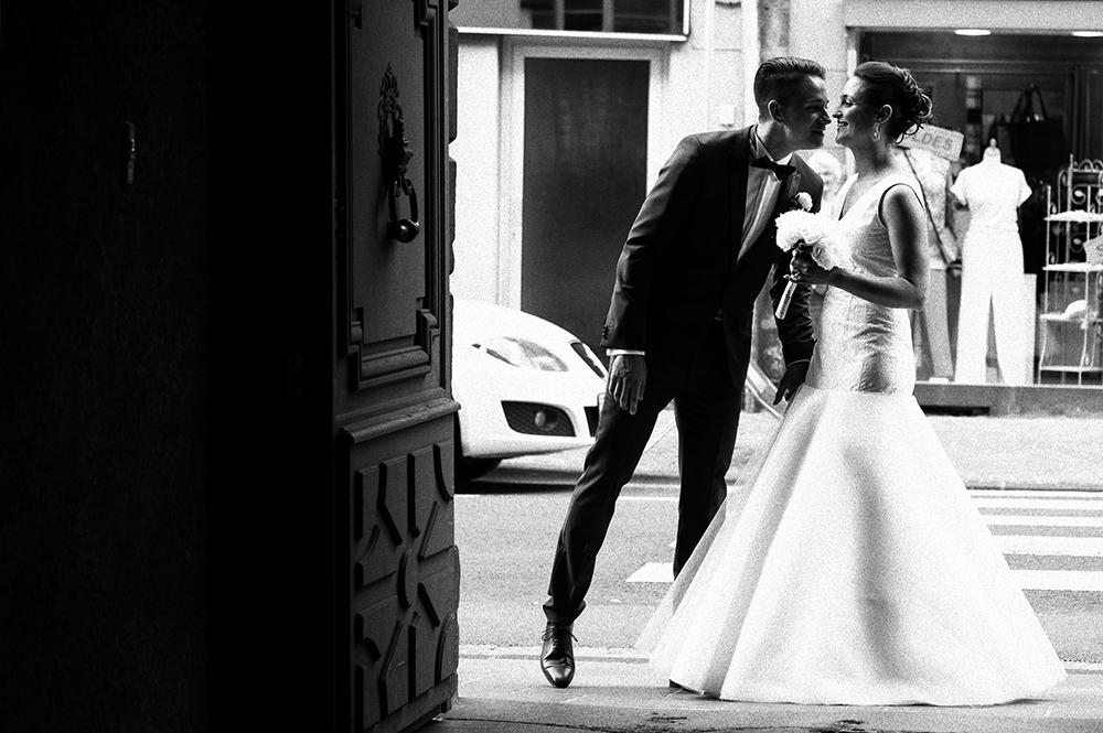 Couple de mariés avant la cérémonie civile devant la mairie de riom. Instant volé de complicité.