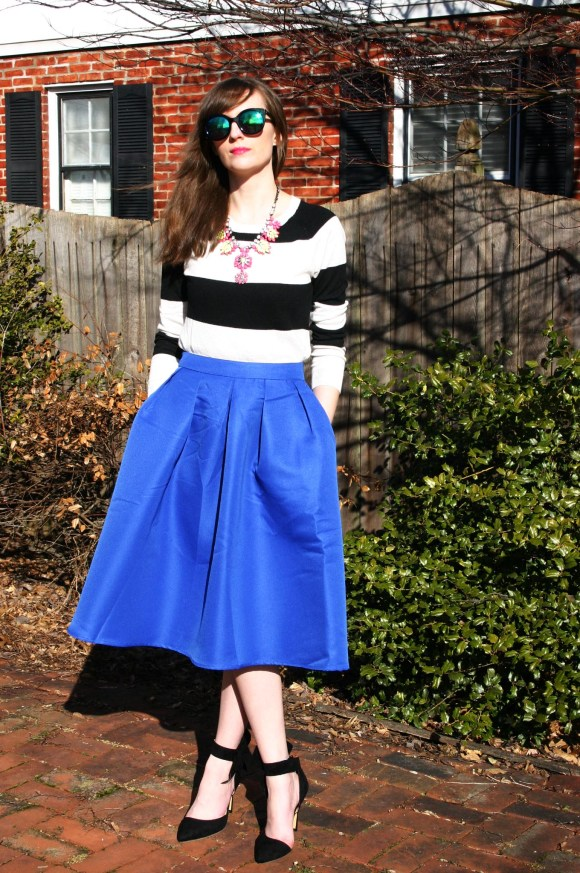 Emily from Fashion By Committee- SheIn blue midi skirt and black bow pumps, Target striped sweater, Call It Spring sunglasses, and Paper Dolls boutique neon statement necklace