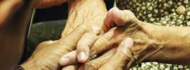 Hands of a Younger holding hands of a senior people on wheelchair