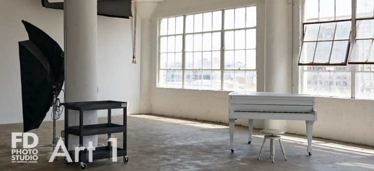natural light photo studio with white staircase, white grand piano, concrete and wood walls
