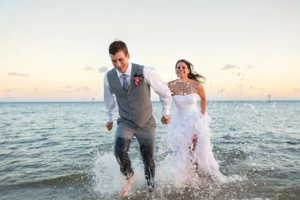bride and groom run in the ocean in key west florida