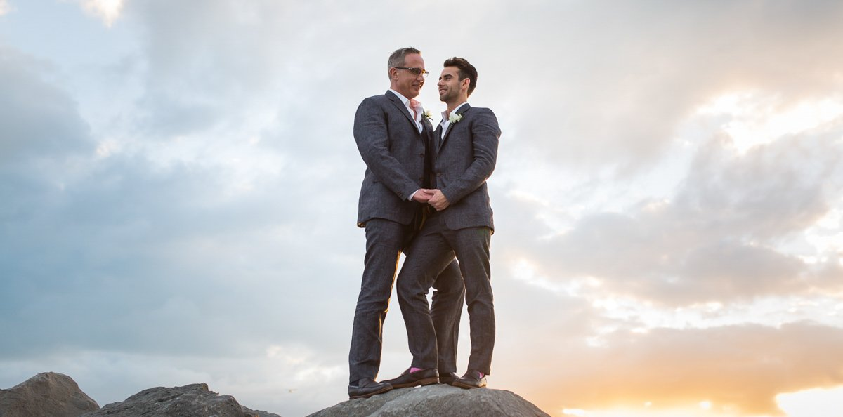 same sex couple on rocks for their wedding photo on key west same sex wedding