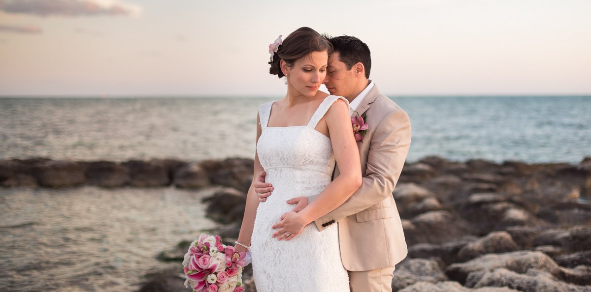 bride and groom on key west beach with ocean and rocks in the background
