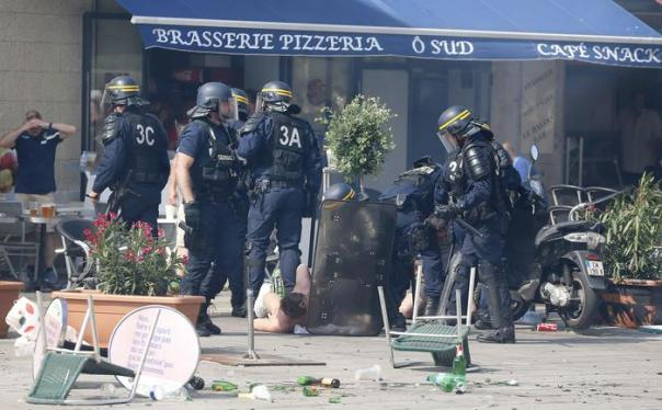 French police officers apprehend soccer supporters during clashes in downtown Marseille, France, Saturday, June 11, 2016. Riot police have thrown tear gas canisters at soccer fans Saturday in Marseille's Old Port in a third straight day of violence in the city. (ANSA/AP Photo/Darko Bandic)