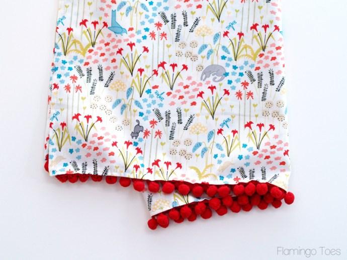 sewing pom pom trim on apron
