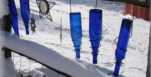 lue bottles wired between the gaps in split-rail fence, by Jeanne Sammons