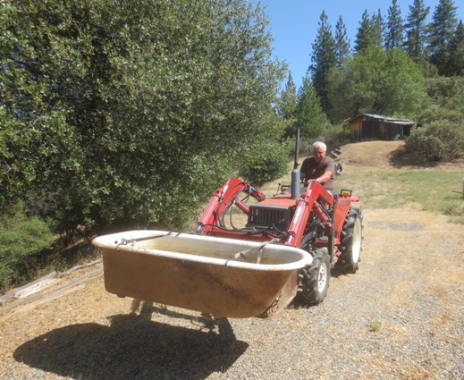 Pried out of it's spot, the tub is transported down from the goat shed