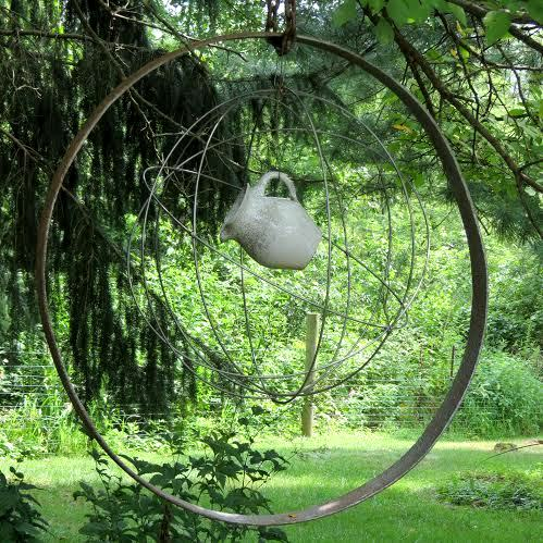 A unique sphere made from wheel rims hangs along the path near a pond.