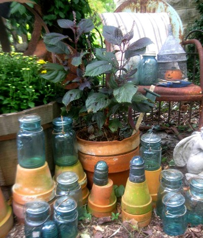 Insulators and mossy covered pots. See the little pumpkin in a funnel 'cage'