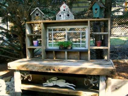 """Barbara Fruehe says, """"My hubby built this from wood someone tossed out, birdhouses from yard sales, purchased old window, and odds and ends from our garden!"""""""