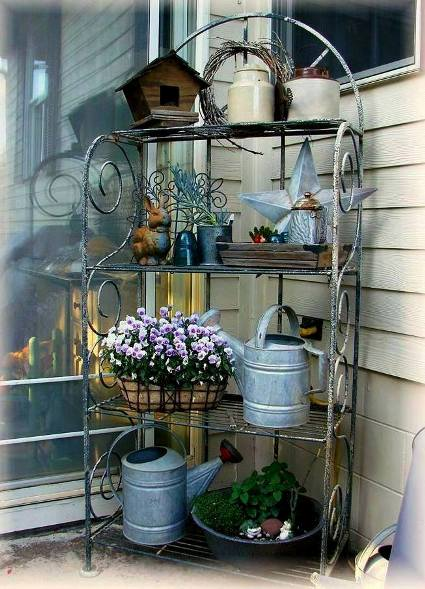 Jeanne Sammons shows off the galvanized watering cans and star in her Baker's rack