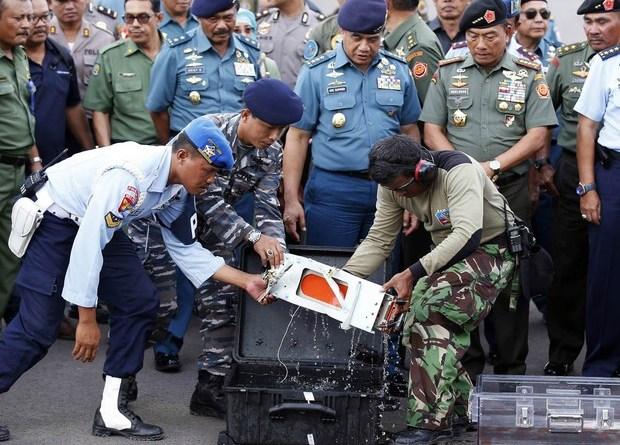 Caixa-preta do voo da AirAsia QZ8501 é transferida para um compartimento transparente após chegar à base aérea de Pangkalan Bun, na Indonésia. O equipamento foi encontrado por mergulhadores e deve ajudar a esclarecer o acidente aéreo (Foto: Darren Whiteside/Reuters)