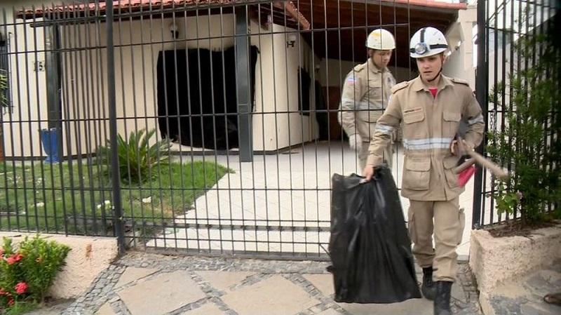 Bombeiros saem com sacos plásticos de casa onde crianças morreram em Linhares (Foto: Reprodução / TV Gazeta)