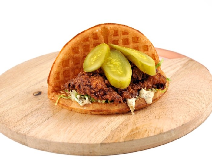 This handheld treat tucks a spicy chicken cutlet, shredded lettuce and pickles between a crispy waffle. (Photo credit: Bruxie)