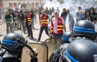 Demonstrators face riot police during a protest in Lyon, central France, Tuesday, May 17, 2016. Truckers blocked French highways and workers marched through city streets Tuesday to protest longer working hours, but President Francois Hollande is insisting he won't abandon the labor reforms that sparked their anger. (ANSA/AP Photo/Laurent Cipriani)