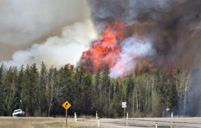 Flames a smoke rise from a wildfire in Fort McMurray, Alberta, Friday, May 6, 2016. More than 80,000 people have left Fort McMurray in the heart of Canada oil sands, where the fire has torched over 1,000 homes and other buildings. (Jason Franson /The Canadian Press via AP) MANDATORY CREDIT