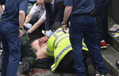 "Conservative Member of Parliament Tobias Ellwood, centre, helps emergency services attend to an injured person outside the Houses of Parliament, London, Wednesday, March 22, 2017. London police say they are treating a gun and knife incident at Britain's Parliament ""as a terrorist incident until we know otherwise."" The Metropolitan Police says in a statement that the incident is ongoing. It is urging people to stay away from the area. Officials say a man with a knife attacked a police officer at Parliament and was shot by officers. Nearby, witnesses say a vehicle struck several people on the Westminster Bridge. (Stefan Rousseau/PA via AP)."