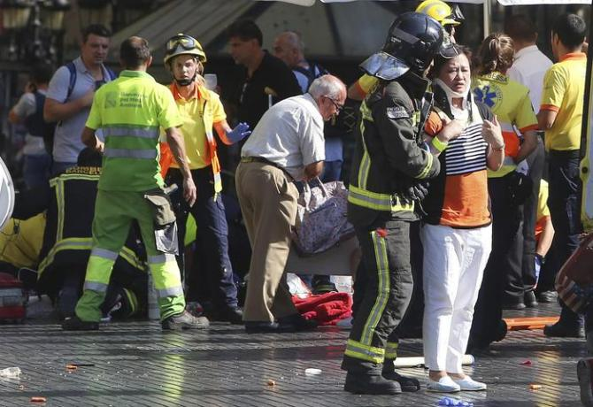 Injured people are treated in Barcelona, Spain, Thursday, Aug. 17, 2017 after a white van jumped the sidewalk in the historic Las Ramblas district, crashing into a summer crowd of residents and tourists and injuring several people, police said. (ANSA/AP Photo/Oriol Duran) [CopyrightNotice: Copyright 2017 The Associated Press. All rights reserved.]