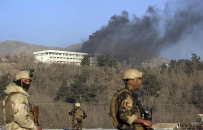 Afghan security personnel stand guard as black smoke rises from the Intercontinental Hotel after an attack in Kabul, Afghanistan, Sunday, Jan. 21, 2018. Gunmen stormed the hotel and sett off a 12-hour gun battle with security forces that continued into Sunday morning, as frantic guests tried to escape from fourth and fifth-floor windows. (ANSA/AP Photo/Rahmat Gul) [CopyrightNotice: Copyright 2018 The Associated Press. All rights reserved.]