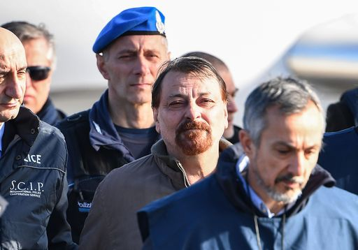 TOPSHOT - Italian former communist militant Cesare Battisti (C), wanted in Rome for four murders attributed to a far-left group in the 1970s, is escorted by Italian Police officers after stepping off a plane coming from Bolivia and chartered by Italian authorities, after landing at Ciampino airport in Rome on January 14, 2019. - Former communist militant Cesare Battisti landed in Rome on January 14 after an international police squad tracked the Italian down and arrested him in Bolivia, ending almost four decades on the run. (Photo by Alberto PIZZOLI / AFP)