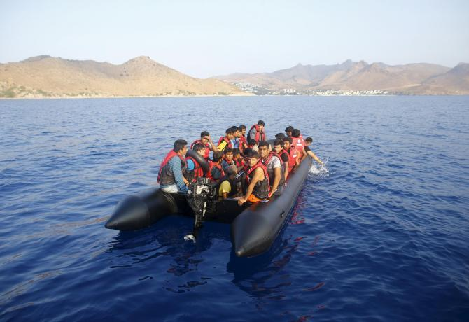 """Migrants on a dinghy with a broken motor drift away as they try to reach the Greek Island of Kos after leaving Bodrum, Turkey, in the hopes of crossing the Mediterrean Sea, September 20, 2015. Many refugees attempt to use Turkey as a springboard into wealthier Europe. A record 300,000 or more Syrians and other migrants have arrived in Greece, mostly setting off from Turkey's Aegean coast, according to the International Organisation for Migration. The coastguard has rescued more than 53,000 migrants while 274 have died in Turkish waters, Kurtulmus has said, without specifying a time frame. The """"captains"""" of the migrant dinghies are often immigrants themselves, with no experience on the sea. REUTERS/Umit Bektas"""