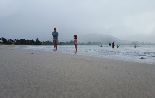 A mother and her daughter enjoy a rainy day at the beach in Hanalei Bay last December.