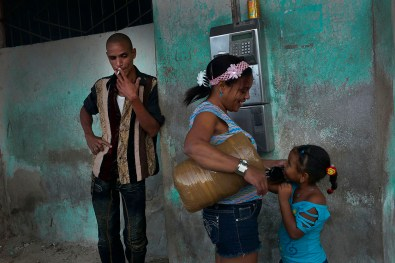 Little girl calling her grand-mother. Cubans often use public phones as cellular phones are not common. The family is waiting for the bus and while waiting the mother let her daughter talk to her grand-mother. Habana Vieja, November, 2013
