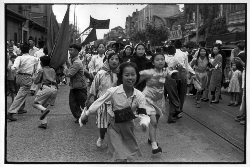 """CHINA. Shanghai. 1949.Ê """"Des Žtudiants dansent le """"Yanko"""" dans un dŽfilŽ. Les paysans du Nord avaient depuis longtemps l'habitude de chanter et de danser le """"Yanko"""" au printemps, ˆ l'Žpoque des semailles. Mais le """"Yanko"""" fut adoptŽ par les armŽes populaires, les suivit dans leur avance, et se propagea dans tout le pays. Sa vogue fut extraordinaire et beaucoup de produits commerciaux prirent le mot """"Yanko"""" comme marque publicitaire."""" Cartier-Bresson Since July 1946, China has been torn apart by civil war between the Communist forces of MAO TSE-TUNG and the Nationalist forces (Kuomintang) of General TCHANG KAI CHEK. Slowly the Communist gained terrain and take the controll of Shanghai the 27th of May."""