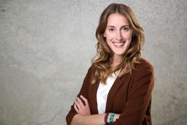 Bewerbungsbild von einer Frau vor grauer Wand mit struktur.