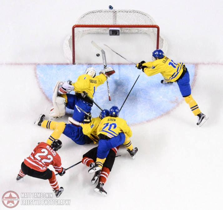 The puck gets past Sweden's Filip Gustavsson #1 for a Canada third period goal while Timothy Liljegren #19 reaches for the puck and Canada's Michael Mcleod #22, Sweden's Oskar Steen #20 and Jacob Moverare #6 get tangled up in front of the net during semifinal round action at the 2016 IIHF Ice Hockey U18 World Championship. (Photo by Matt Zambonin/HHOF-IIHF Images)