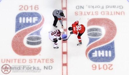 Latvia's Deniss Smirnovs #10 and Switzerland's Andre Heim #26 face off during preliminary round action at the 2016 IIHF Ice Hockey U18 World Championship. (Photo by Matt Zambonin/HHOF-IIHF Images)
