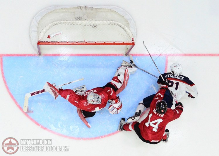 Switzerland's Ludovic Waeber #1 makes a skate save off a shot from USA's Ryan Hitchcock #21 as he's checked to the ice from Switzerland's Dario Meyer #14 during preliminary round action at the 2016 IIHF World Junior Championship. (Photo by Matt Zambonin/HHOF-IIHF Images)